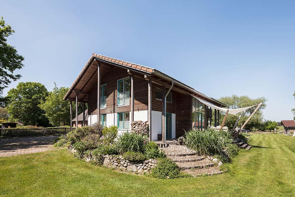 Holzhaus Bassen, Außenansicht mit dunkler Holzverschalung und breitem Dachüberstand