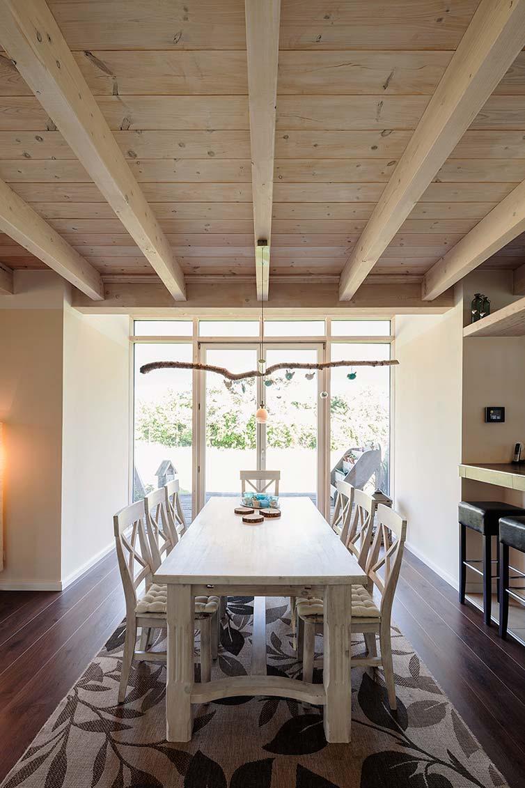 Holzhaus Bassen, massive Holzbalkendecke und breite Landhausdielen im Essbereich