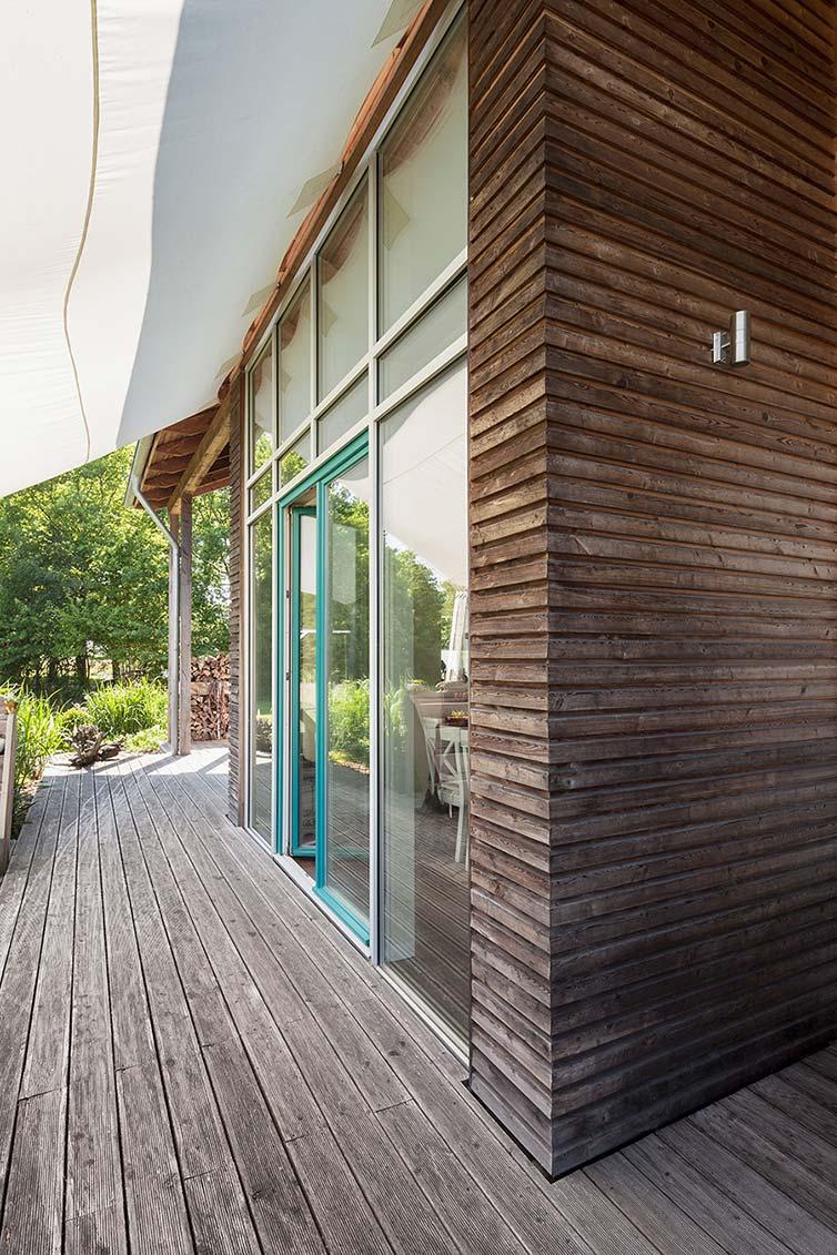 Holzhaus Bassen, umlaufender Terrassenbereich mit natürlich vergrauter Fassade