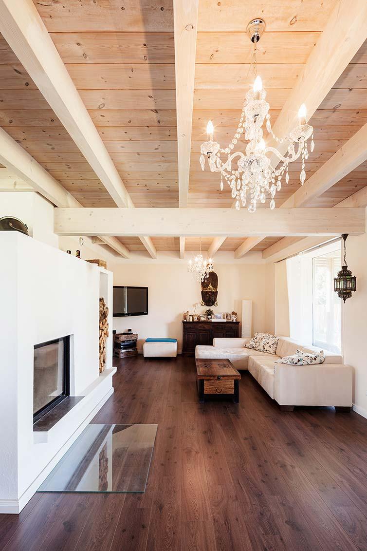 Holzhaus Bassen, Wohnzimmerbereich mit Grundofen und Holzbalkendecke in Sichtausführung